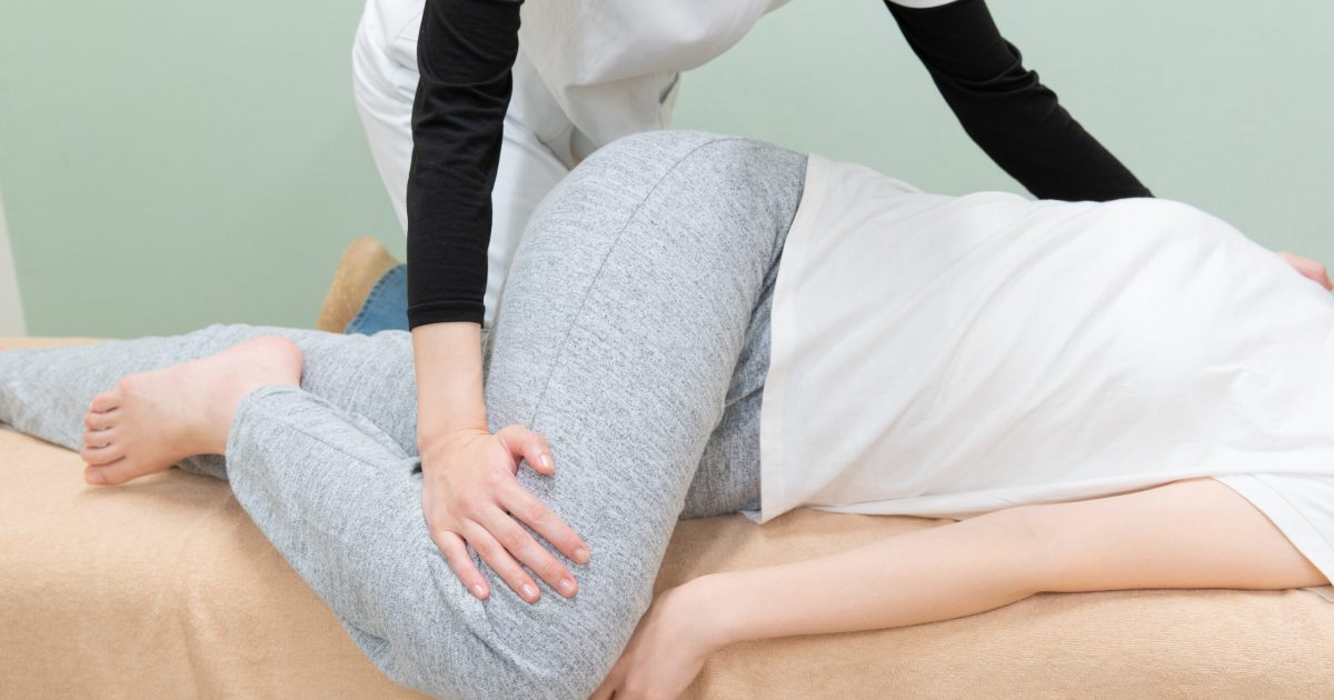 Asian female practitioner massaging waist and palvis of female patient